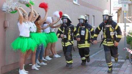 Kein ungewöhnliches Bild in Aindling: Cheerleader feuern Feuerwehrmänner an. Unter der Ausrüstung dürfte es auch bei diesen Temperaturen heiß geworden sein.