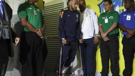 Neymar (M) verlässt die Umkleidekabine der Brasilianer an Krücken, nachdem er sich während des Spiels gegen Katar verletzt hat. Foto: Andre Penner/AP