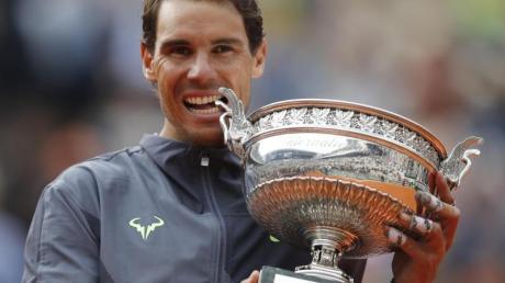 Rafael Nadal beißt nach seinem Sieg in die Trophäe. Foto: Christophe Ena/AP