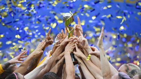 Die US-Spielerinnen feiern ihren Sieg und halten gemeinsam den WM-Pokal nach oben. Foto: Sebastian Gollnow