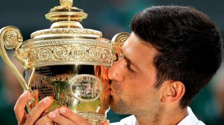 Novak Djokovic küsst bei der Siegerehrung die Trophäe für den Finalgewinner. Foto: Mike Egerton/PA Wire
