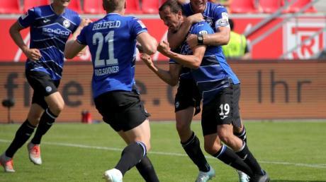 Die Spieler von Arminia Bielefeld freuen sich nach dem Sieg in Regenburg über die Tabellenführung.