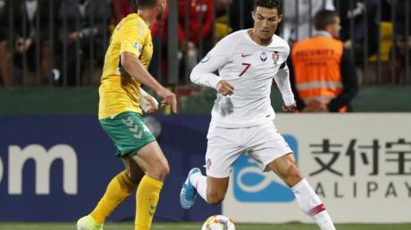 Cristiano Ronaldo (r) im Duell mit dem Litauer Saulius Mikoliunas. Foto:Mindaugas Kulbis/AP