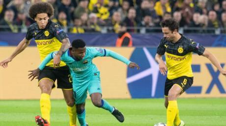 Die Dortmunder Axel Witsel (l) und Thomas Delaney (r) nehmen Ansu Fati vom FC Barcelona den Ball ab. Foto: Bernd Thissen