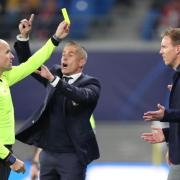 Schiedsrichter Antonio Mateu Lahoz (l) zeigt Leipzigs Trainer Julian Nagelsmann (r) die Gelbe Karte, dahinter gestikuliert Lyons Trainer Sylvinho. Foto: Jan Woitas/dpa-Zentralbild/dpa