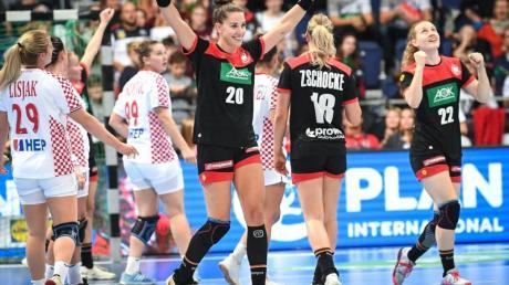 Deutschlands Emily Bölk (M-r), Mia Zschocke und Maren Weigel jubeln nach der ersten Halbzeit. Foto: Sina Schuldt/dpa
