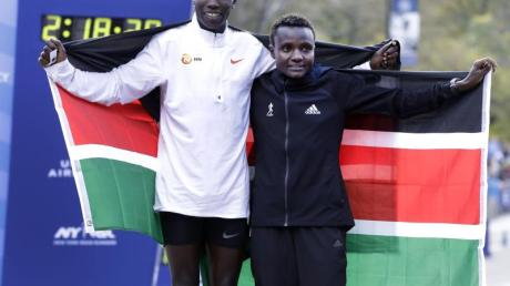 Die Kenianer Geoffrey Kamworor und Joyciline Jepkosgei posieren während der Siegerehrung mit den Landesfarben.