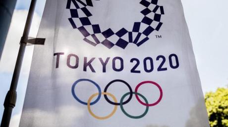 Das Logo für die Olympischen Sommerspiele Tokyo 2020 auf einer Fahne. Foto: Michael Kappeler/dpa