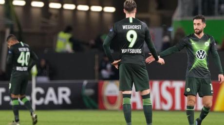 Wolfsburgs Victor Joao (l-r), Wout Weghorst und Yunus Malli stehen nach dem Spiel gegen Gent auf dem Rasen. Foto: Peter Steffen/dpa