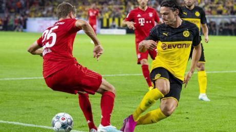 Treffen im Bundesliga-Topspiel aufeinander: Dortmunds Nico Schulz (r) und Bayerns Thomas Müller. Foto: Guido Kirchner/dpa