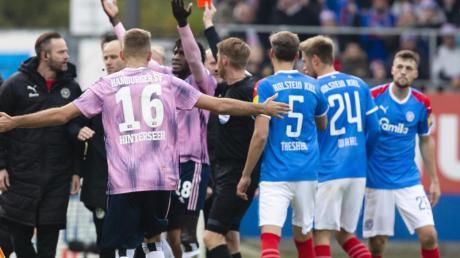 Schiedsrichter Christian Dingert (M) zeigt Hamburgs Bakery Jatta die Rote Karte. Foto: Frank Molter/dpa