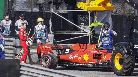 Sebastian Vettel kann nur missmutig zuschauen, wie sein Ferrari von einem Abschleppkran zurück in die Box gebracht wird.