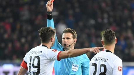 Schiedsrichter Felix Brych zeigt David Abraham nach einem Foul an Freiburgs Trainer Christian Streich die Rote Karte. Foto: Patrick Seeger/dpa
