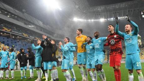 Die Wolfsburger Spieler feiern nach Abpfiff mit den Fans den Sieg.