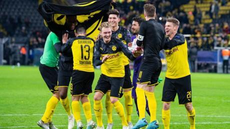 Nach dem Spiel gegen Slavia Prag tanzen Dortmunds Spieler erleichtert vor den Fans auf dem Spielfeld.