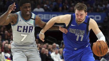 Dwayne Bacon (7/l) von den Charlotte Hornets attackiert Mavs-Spieler Luka Doncic (77).
