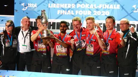 Glücklich über ihren ersten Pokalerfolg beim Tischtennis-Final-Four in Neu-Ulm: Team und Betreuerstab des ASV Grünwettersbach bei der Siegerehrung in der Ratiopharm-Arena. Der ASV musste sich als Außenseiter drei Topteams der Bundesliga stellen.