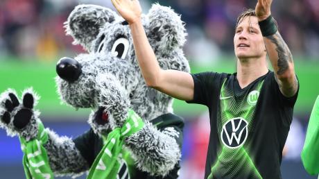 Wolfsburgs Stürmer Wout Weghorst und das VfL-Maskottchen Wölfi zeigen es an: Es geht wieder los in der Bundesliga. Das Eröffnungsspiel bestreiten Schalke 04 und Mönchengladbach.