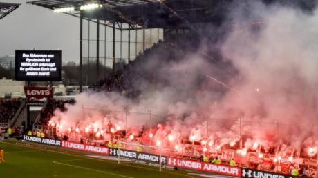 Fans brennen beim Derby zwischen dem FC St. Pauli und dem Hamburger SV Pyrotechnik ab, während eine Anzeigetafel genau davor warnt.