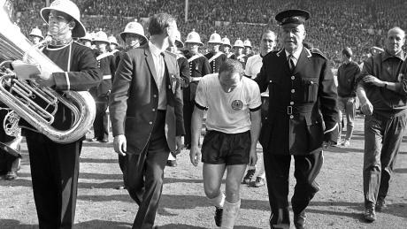 Während Helmut Schön (rechts) im Moment der Niederlage die Ärmel hochkrempelt, verlässt Uwe Seeler geknickt das Spielfeld.