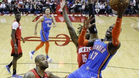 Dennis Schröder (r/17) von den Oklahoma City Thunder setzt sich am Korb gegen Ben McLemore (M) von den Houston Rockets durch.