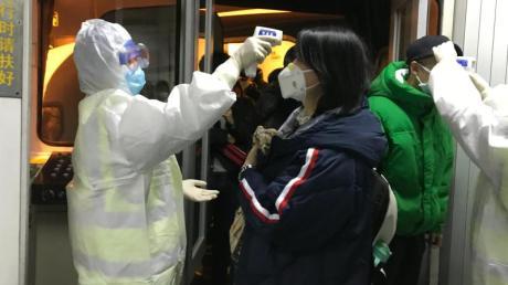 Gesundheitsbeamte kontrollieren am Flughafen von Peking die Körpertemperatur von Reisenden aus der Stadt Wuhan.
