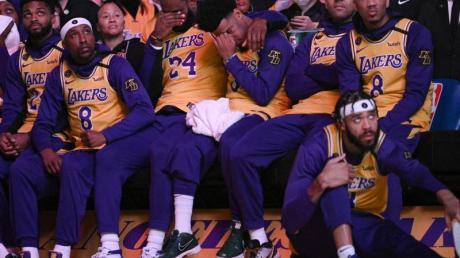 LeBron James (M,l) und Quinn Cook (M,r) von den Los Angeles Lakers schlagen bei einem Video-Beitrag über Kobe Bryant die Hände vors Gesicht.