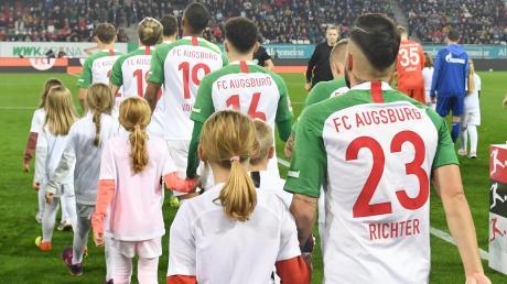 Einmal an der Hand eines Bundesliga-Stars einzulaufen - wie hier beim Heimspiel des FC Augsburg gegen den FC Schalke - ist für viele Kinder  einer der sehnlichsten Wünsche.