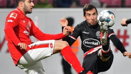Der Mainzer Levin Ötztunali (l) und Düsseldorfs Markus Suttner kämpfen um den Ball.