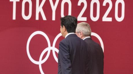 Japans Premierminister Shinzo Abe (l) und IOC-Präsident Thomas Bach sollen sich auf die Verschiebung der Olympischen Spiele in Tokio um ein Jahr verständigt haben.
