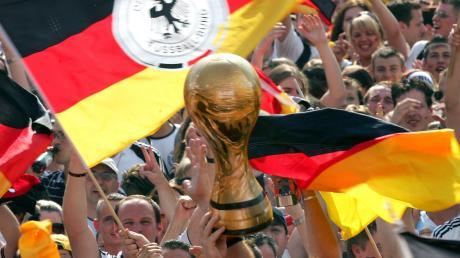 Deutschland im Sommer 2006: Fans schwenken Fahnen und jubeln einer Nachbildung des WM-Pokals auf der Fanmeile in Berlin zu.