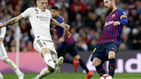 Auch für Toni Kroos (l) und Lionel Messi soll in Spanien der Ball bald wieder rollen.