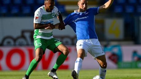 Der Fürther Julian Green (l) hält Fabian Schnellhardt im Zweikampf fest.
