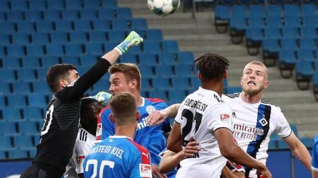 Der Kieler Torwart Ioannis Gelios (l-r) faustet den Ball vor seinen Teamkameraden Phil Neumann, Hauke Wahl und den Hamburgern Josha Vagnoman und Rick van Drongelen weg.
