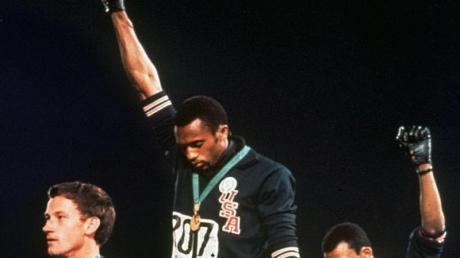 Die US-Athleten Tommie Smith (M) und John Carlos (r) streckten während Olympia 1968 die Fäuste, um gegen Rassismus zu protestieren.
