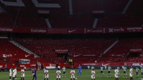Spieler des FCSevilla und Real Betis Sevilla legen eine Schweigeminute für die Coronavirus-Todesopfer ein.