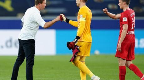 Leipzigs Trainer Julian Nagelsmann (l) klatscht sich nach dem Sieg mit Torwart Peter Gulacsi (M.) und Lukas Klostermann ab.