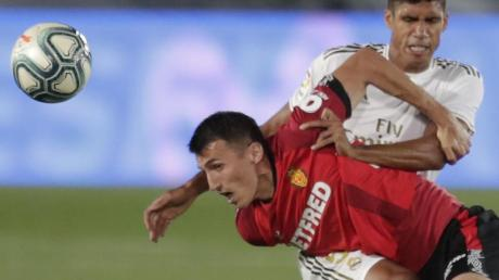 Raphael Varane (r) von Real Madrid kämpft gegen Ante Budimir (l) vom RCD Mallorca um den Ball.