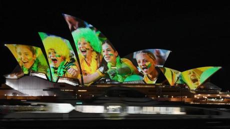 Australien und Neuseeland sind die Gastgeber der Frauenfußball-Weltmeisterschaft 2023: Das Opernhaus wird mit leuchtenden bunten Fotos von Fußball-Fans angestrahlt.