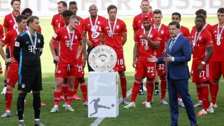 Christian Seifert überreicht nach einer denkwürdigen Saison den Bayern-Profis die Meisterschale.