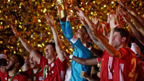 Münchens Torhüter Manuel Neuer hält die Trophäe jubelt mit demDFB-Pokal.