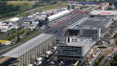 Ein Blick von oben auf den Nürburgring und die Start-Ziel-Gerade sowie das Fahrerlager (links). Im Hintergrund thront die Nürburg, die Namensgeber für die Strecke ist. Rechts neben der Strecke sind Teile der Achterbahn zu sehen, die nach wenigen Tagen ihren Betrieb wieder einstellen musste.
