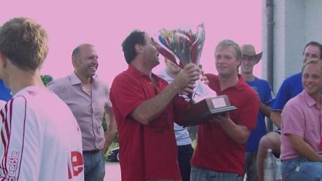 Der zweifache Torschütze beim 5:2-Sieg in Unterglauheim, Thomas Mödinger (rechts), hebt mit einem SSV-Fan den Meisterpokal in die Höhe.