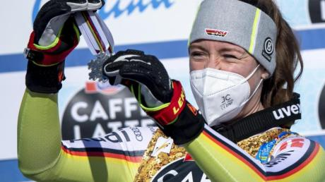 Kira Weidle hängt sich voller Freude die Silbermedaille bei der Siegerehrung selbst um den Hals.
