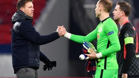 Leipzigs Torwart Peter Gulacsi (M) und Leipzigs Trainer Julian Nagelsmann geben sich nach dem Spielende die Hand.