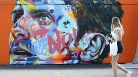 Eine Frau geht an einem Wandbild von Novak Djokovic vorbei, das auf eine Wand im Melbourne Park gemalt wurde.