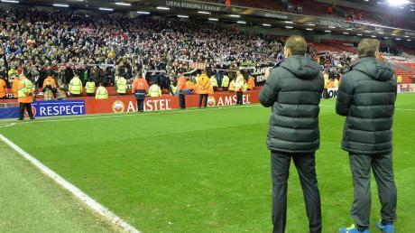 Markus Weinzierl (links) und sein damaliger Co-Trainer Wolfgang Beller stehen vor den FCA-Fans im Auswärtsblock der Liverpooler Anfield Road.
