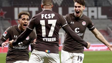 Daniel-Kofi Kyereh (M) feiert seinen Treffer zum 1:0 für den FC St. Pauli gegen den HSV mit Rodrigo Zalazar und Luca Zander (r).