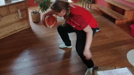 Ballübungen II: Achterkreisen des Basketballes durch die Beine. Magdalena Sredl zeigt, wie es daheim funktioniert.