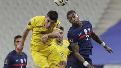 Frankreichs Presnel Kimpembe (r) kämpft mit dem Ukrainer Ruslan Malinowskyj um den Ball.